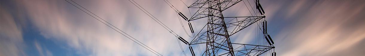 Headerbild Firmengeschichte - Strommasten vor bewöltem Himmel